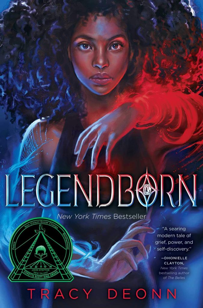 The cover of the book Legendborn by Tracy Deonn depicting a young black woman with natural hair and blue and red magic encircling her arms.
